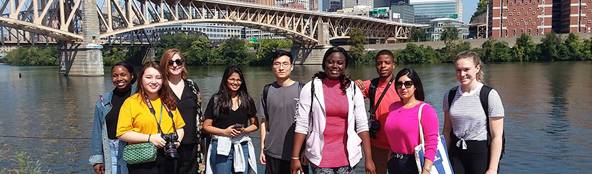 Students stand in front of a bridge in Pittsburgh