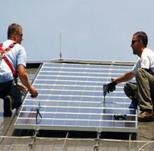 Two men installing a rooftop solar panel
