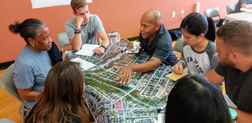 Student interns surrounding a community planning map